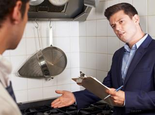 A man with a clipboard talks to a chef in the kitchen.