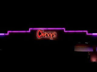 Chevys restaurant sign lit up at night.