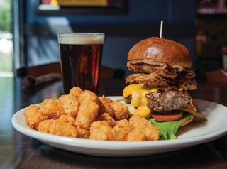 A burger with tater tots and a beer at Bad Daddy's Burger Bar.