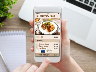 Female hand holding white phone with app delivery food screen.