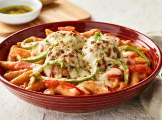 Pasta Georgio features penne pasta with sautéed bell peppers and Romano, tossed in roasted red pepper sauce, then topped and baked with meatballs and mozzarella.