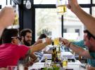 Restaurant customers cheers glasses around a table.