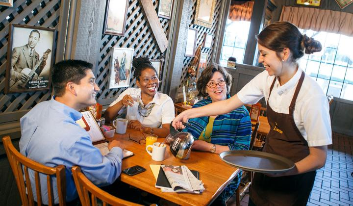 A Cracker Barrel waitress serves guests inside the restaurant.