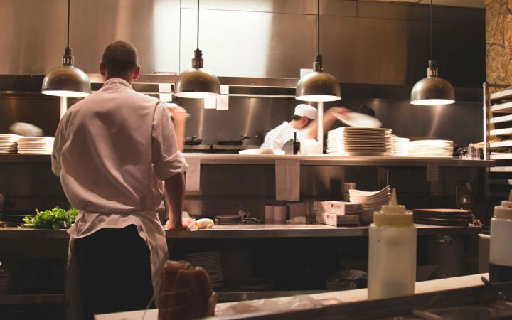 Chefs at work in a restaurant kitchen.