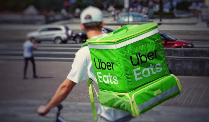 A man rides a bicycle with an UberEats backpack.