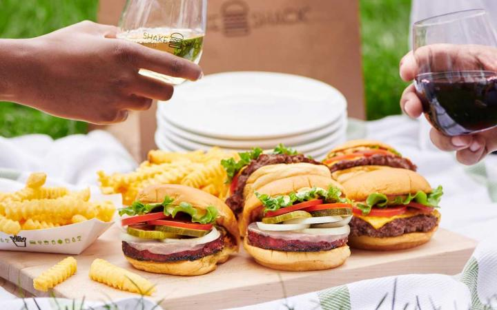 Plate of Shake Shack burgers and glasses of wine
