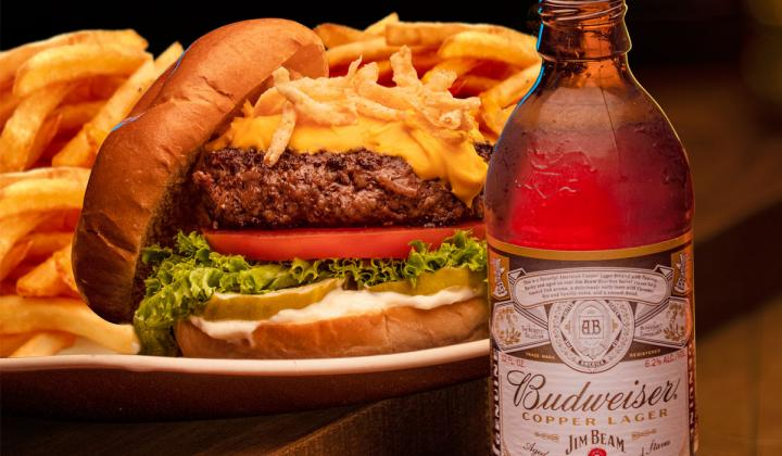 Pimento Cheeseburger next to a bottle of Budweiser beer.