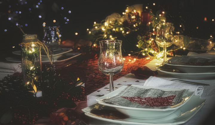 White plate and glass on a Christmas dinner table.