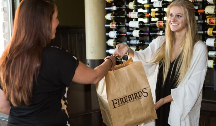 A Firebirds restaurant employee hands a bag of food to a customer.