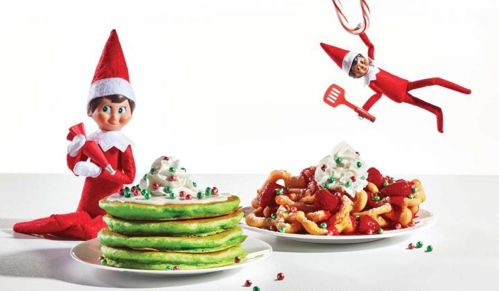 Two Elf on the Shelf dolls with a plate of IHOP pancakes and funnel cake.