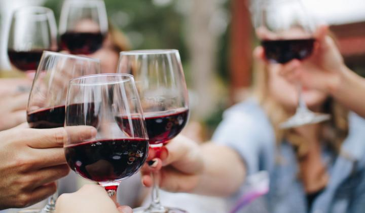 People clink glasses with red wine.