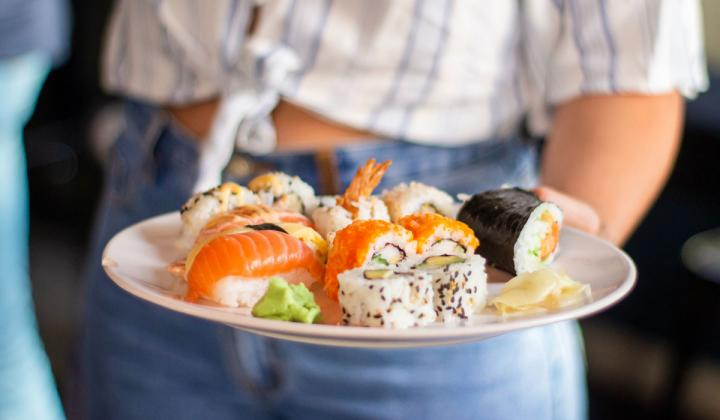 Plate of sushi being carried by a person.