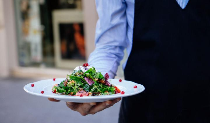Restaurant employee holding a plate of salad.