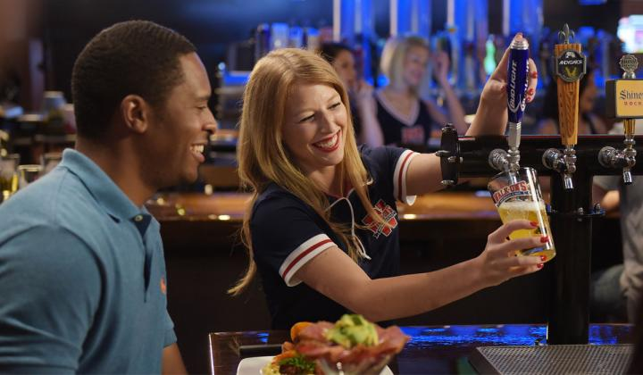 A Walk-On's waitress pours a beer for a customer.