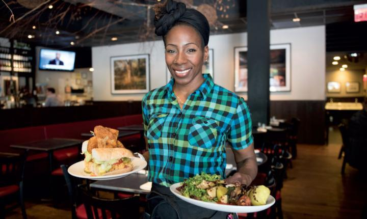 A waitress carries two plates of food.