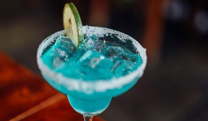 Clear margarita glass with cyan liquid and lime slice.