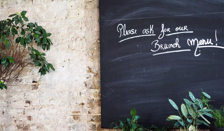 A black board with please ask for our brunch menu! text beside green potted plants.