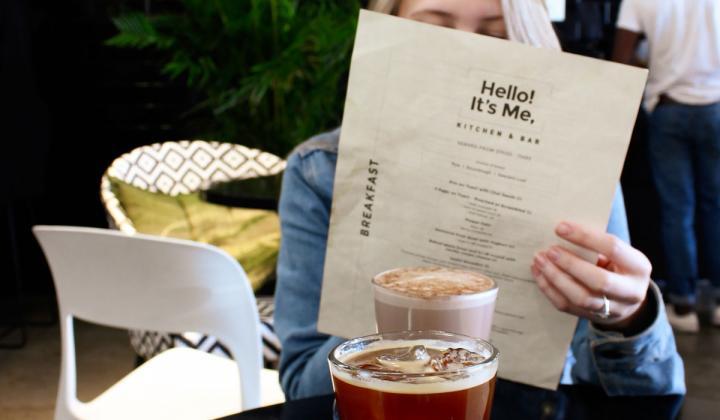 A restaurant customer holds up a menu.
