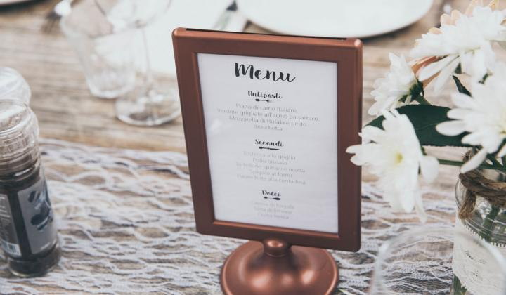 Menu-printed board with brown frame on table.