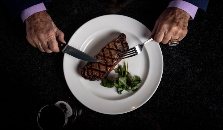 Don Shula cuts a steak.