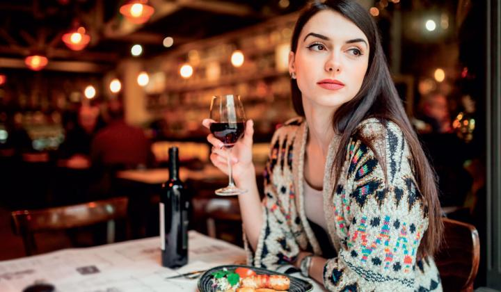 A woman dines alone with a glass of wine at a restaurant.