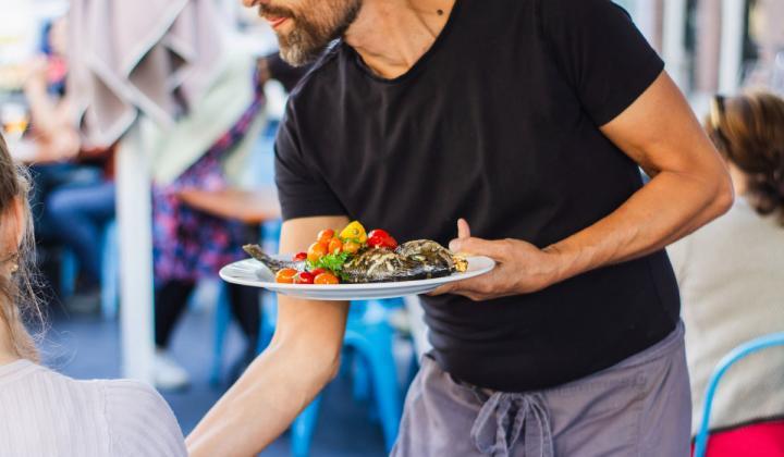 A waiter serves food at a restaurant.