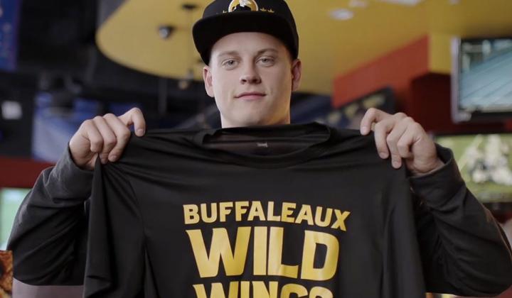 Joe Burrow holds up a Buffalo Wild Wings T-shirt.