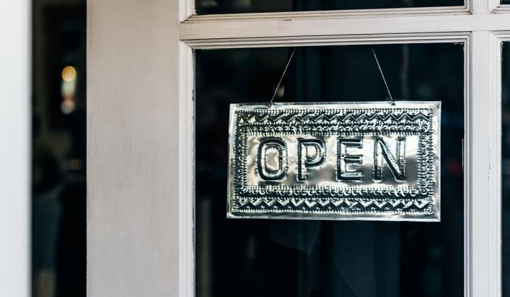 Metal open sign hangs in window.