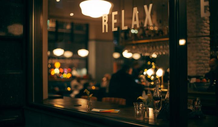 "Person sitting inside restaurant with ""relax"" on the window."