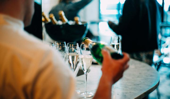 A waiter pours champagne into a glass.