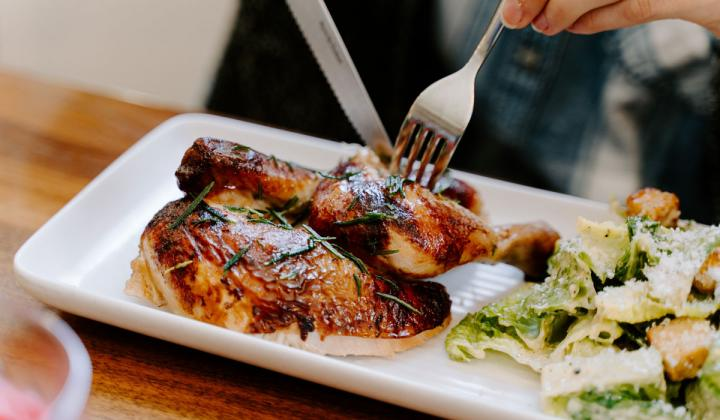 Grilled chicken being cut on a dish.