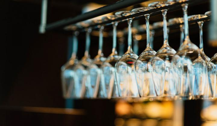 Wine glasses hanging from a rack.
