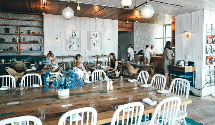 People in cafe with brown tables.