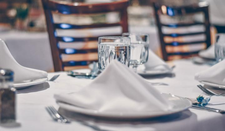 Glass of water on a white tablecloth-covered table.