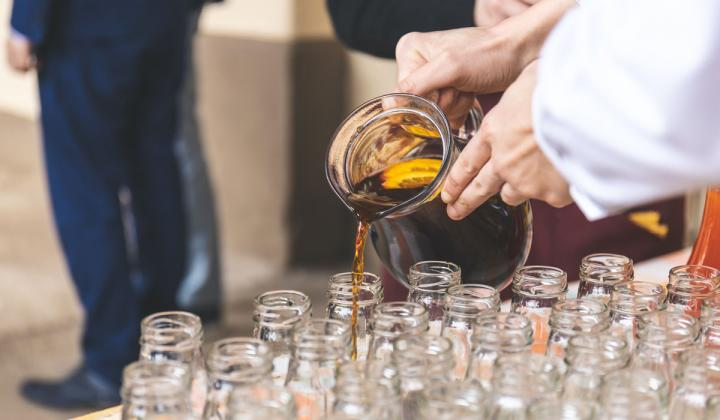 Waiter pours drinks into jars.