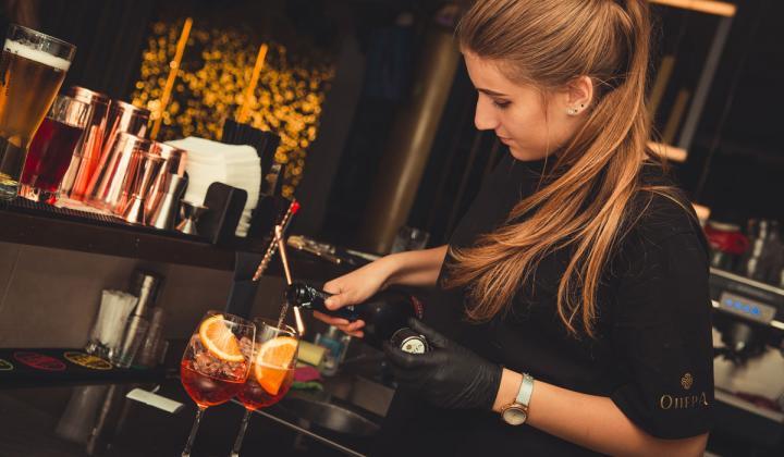 A bartender pours cocktails into glasses.