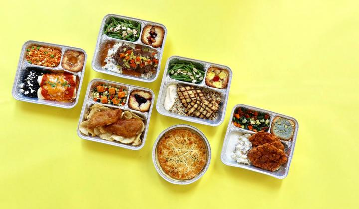 Lazy Dog take-home TV dinners on a yellow background.