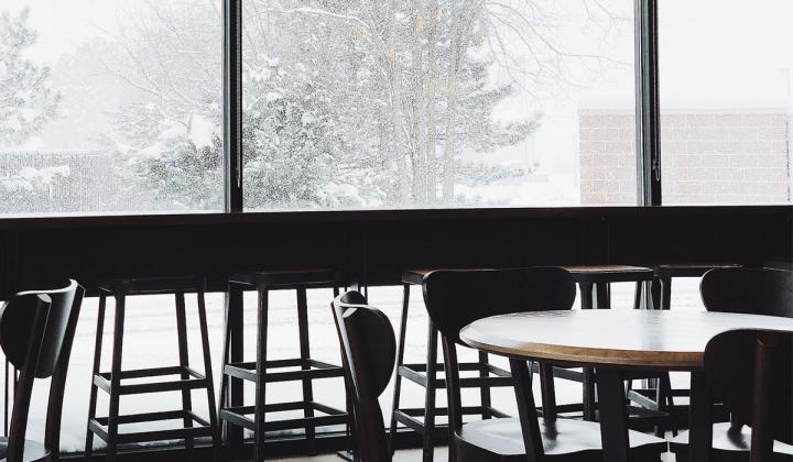 Snow falling outside a restaurant window.