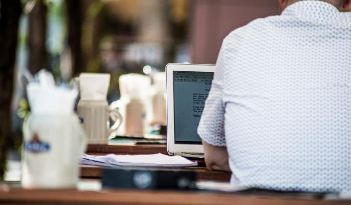 Man looking at a computer while sitting at a table.