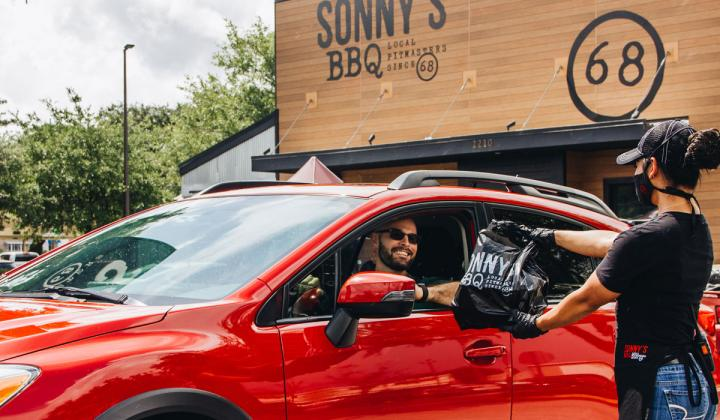 Sonny's BBQ customer gets food at their car.