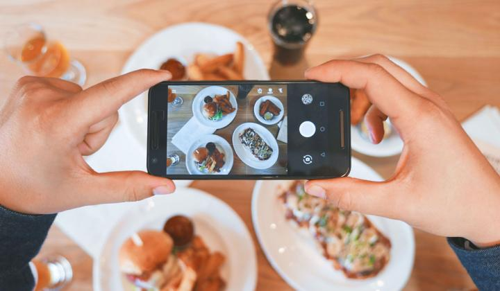 Customer taking a photo of food with their phone.