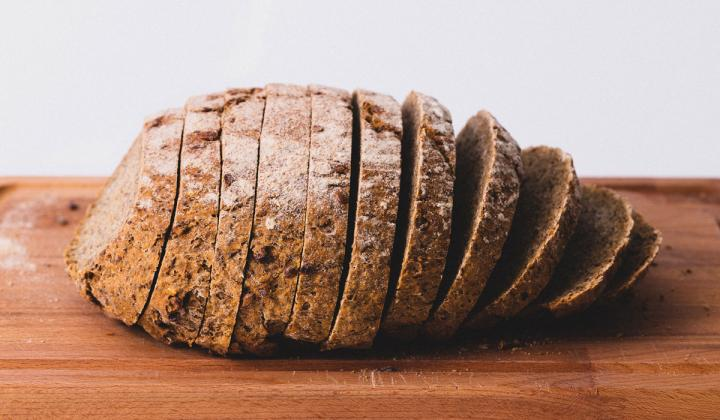 Loaf of brown bread on a wooden table.