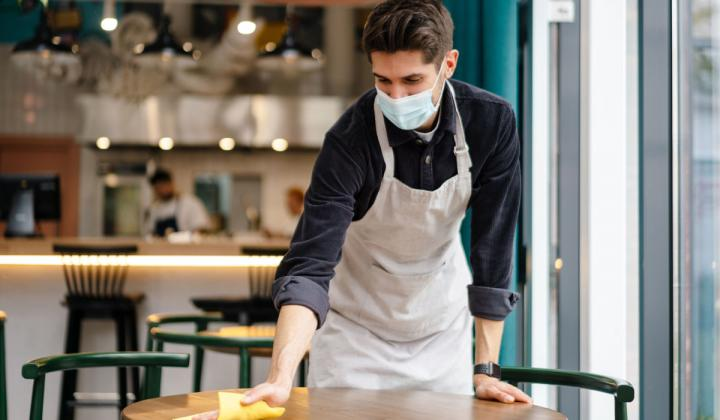 Waiter wearing mask disinfecting table in the cafe.