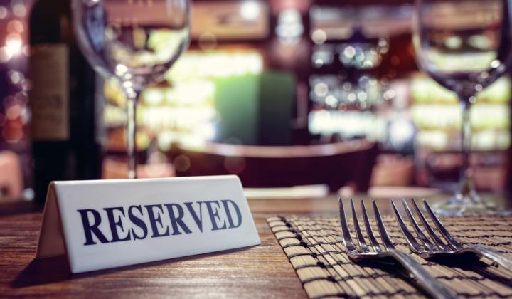 Reserved sign on restaurant table with bar background.