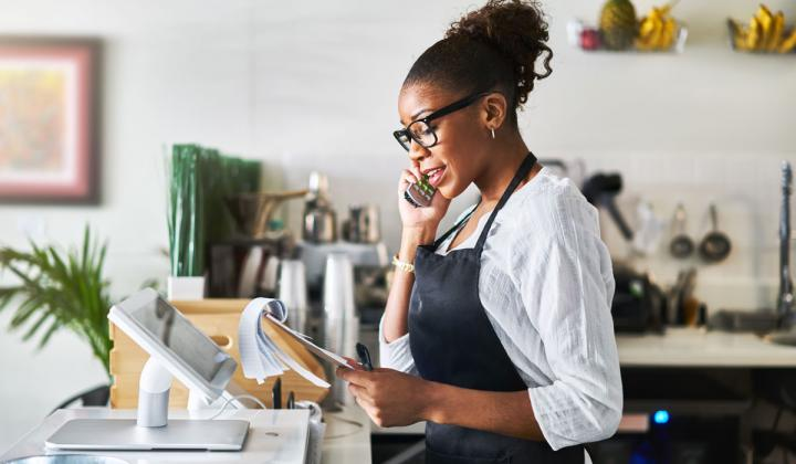 Waitress taking order on phone at restaurant and writing on notepad.