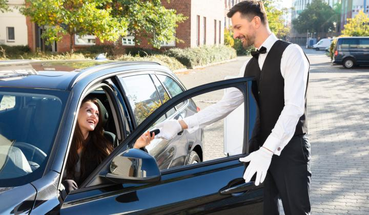 Valet driver getting keys from a customer's car.