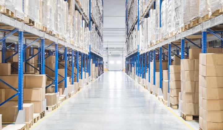 Passageway in a huge distribution warehouse with high shelves.