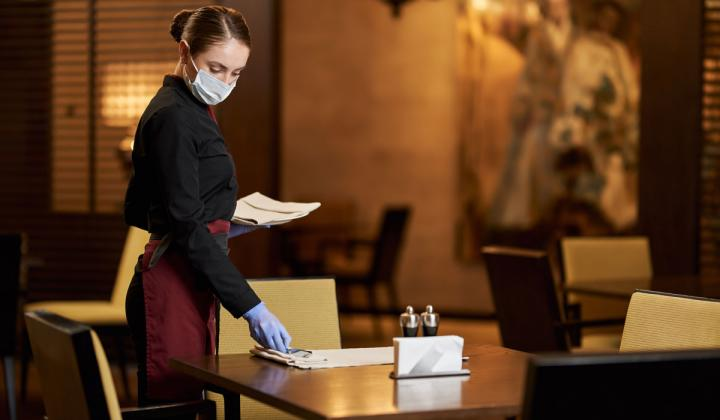 Restaurant server in protective mask preparing table.