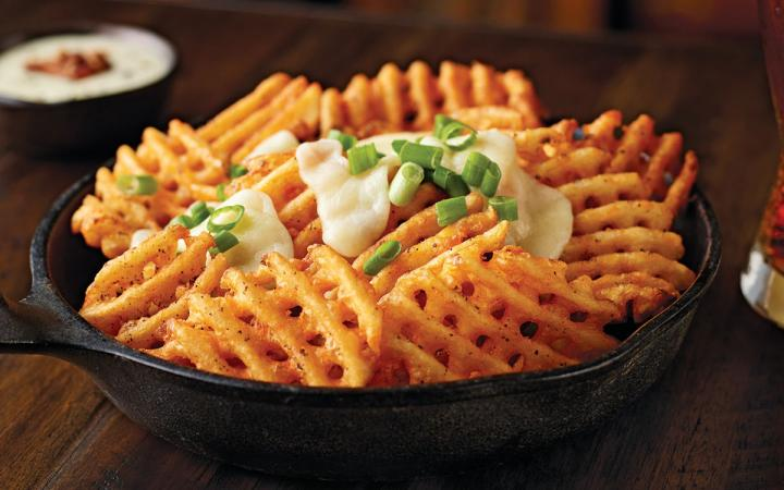 McCain Foodservice's Redstone Canyon fries are served in a cast iron skillet, topped with melted cheese curds and a sprinkling of green onions.