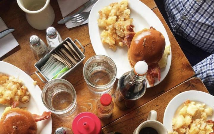 A table with burgers and coffee